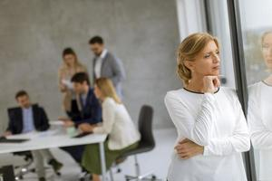 femme regardant par la fenêtre avec une réunion d'affaires derrière elle photo