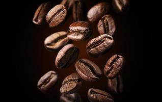 Grains de café torréfiés tombant ou volant sur fond noir se bouchent photo