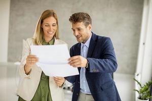 deux professionnels souriant et regardant par-dessus des documents photo