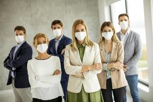 équipe debout et portant des masques photo