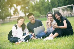 groupe d & # 39; étudiants asiatiques qui étudient dans l & # 39; herbe photo