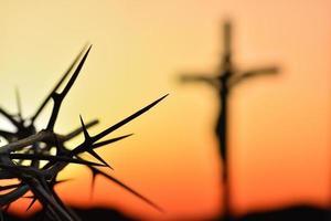 Couronne d'épines de jésus christ contre silhouette de croix catholique au coucher du soleil fond photo