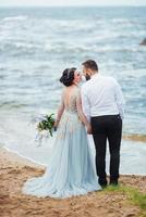 Mariée dans une robe bleue avec le marié marchant le long du rivage de l'océan photo