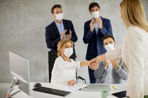 professionnels se serrant la main avec des masques sur photo