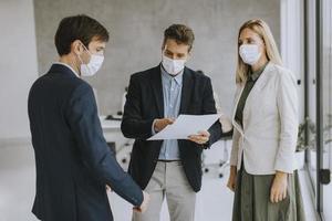 trois professionnels discutant de documents avec des masques sur photo