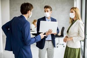 trois professionnels masqués parlant avec un ordinateur portable photo