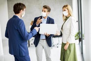 trois professionnels masqués debout et parlant photo