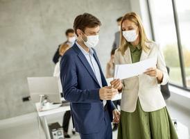 deux professionnels masqués regardant un document photo