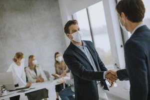 deux hommes d & # 39; affaires masqués se serrant la main photo