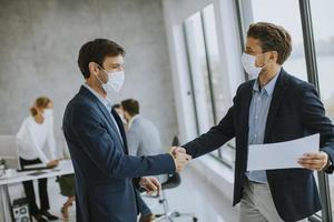 Deux hommes d'affaires masqués se serrant la main en accord photo