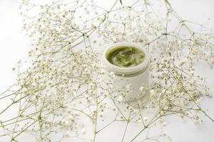 Récipient en plastique ouvert avec de la crème et des fleurs sur fond blanc photo