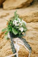 bouquet d'une mariée de roses se trouve sur un grès photo