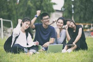 étudiants asiatiques applaudissant sur la pelouse photo