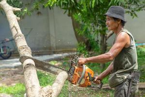 Portrait de l'arboriculteur couper le journal par une scie à chaîne avec de la sciure de bois éclaboussant autour. Mouvement flou de scie à chaîne photo