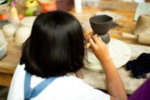 Gros plan des mains de petite fille le moulage de l'argile sur le plateau de roue par bâton en bois avec dos flou portrait de jeune fille en premier plan photo