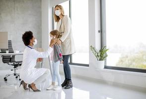 pédiatre donnant à la fille un examen médical photo