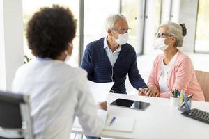 médecin discutant des soins avec un couple d'âge mûr photo