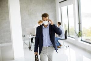 homme d & # 39; affaires marchant et prenant le téléphone avec un masque sur photo