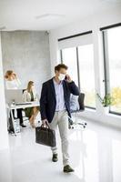 vue verticale d'un homme d'affaires masqué prenant le téléphone et tenant une mallette photo