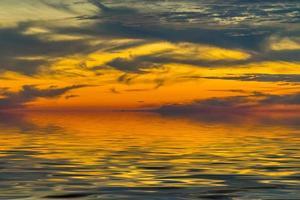 paysage d'une hauteur surplombant la mer et un coucher de soleil lumineux photo