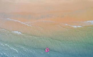 Vue aérienne de dessus du drone vue du garçon avec anneau de bain dans la mer et l'ombre bleu émeraude de l'eau et de la mousse de vague au lever du soleil photo