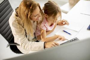vue de dessus d'une mère travaillant avec sa fille sur ses genoux photo