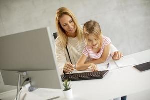 mère travaillant avec sa fille sur ses genoux photo