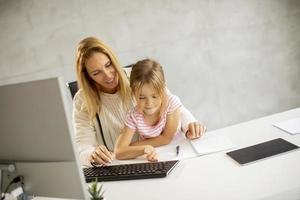 mère essayant de travailler avec sa fille sur ses genoux photo