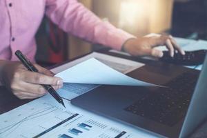 Concepts de comptabilité de teneur de livres, calculatrice d'utilisation masculine, stylo et ordinateur portable pour travailler les finances et le budget, concept d'inspecteur comptable. photo
