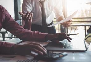 discussions de recherche économique, équipe commerciale analysant les tableaux et graphiques des revenus pour planifier le concept de marketing avec l'utilisation d'un ordinateur portable et d'une calculatrice pour l'analyse. photo