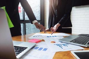 discussions d'affaires économiques, équipe commerciale analysant les tableaux et graphiques des revenus pour planifier le concept de marketing avec l'utilisation d'un ordinateur portable et d'une tablette pour l'analyse. photo