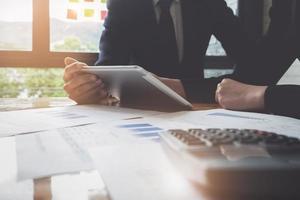 L'équipe commerciale analyse des tableaux et des graphiques de revenu pour planifier le concept de marketing à l'aide de la tablette et de la calculatrice pour l'analyse photo