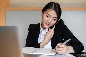 femme d'affaires appelant et travaillant au bureau pour vérifier l'exactitude du compte à l'aide d'une calculatrice et d'un ordinateur portable photo