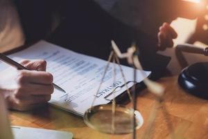 Avocat femme stylo hoding avec contrat ou accord au client pour la signature dans la salle d'audience juridique photo
