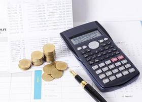 Calculatrice et pile de pièces d'argent avec stylo-plume pour le concept de finance photo
