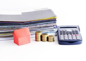 Papier maison rouge et pile de pièces et calculatrice et bordereau de paiement de facture pour le concept de prêts photo