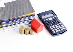 Calculatrice et papier de la maison rouge et pile de pièces et paiement de factures pour le concept de prêts d'argent photo