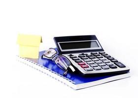 maison de papier et lunettes et calculatrice sur ordinateur portable pour fond de concept d'entreprise photo
