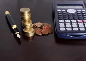 Stylo-plume et pile de pièces et calculatrice sur table en bois pour le concept de finance photo