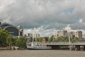 Vue sur les ponts du jubilé d'or et la gare de Charing Cross de la rive sud de la Tamise à Londres par un jour d'été nuageux photo