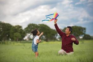 enfant et père jouant avec un cerf-volant dans le parc photo