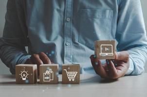 shopping concept d'entreprise en ligne. main de l'homme tenant un cube en bois avec une icône pour faire du shopping. marketing des affaires en ligne. photo