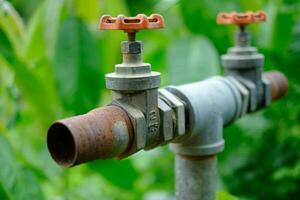 Vanne d'arrêt sur la canalisation dans les systèmes d'irrigation contrôler l'eau pour fermer l'ancien endroit avec un arrière-plan flou photo