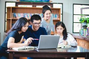 étudiants asiatiques travaillant dans la bibliothèque photo