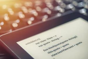 Vue de haut d'un lecteur de livre électronique avec des leçons de programmation sur un clavier d'ordinateur portable dans une école de codage photo