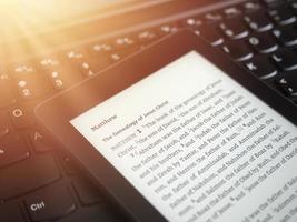 Close up of ebook reader avec la sainte bible sur un clavier d'ordinateur portable avec des rayons de soleil lumière concept photo