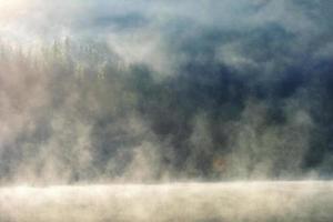 Paysage d'automne dans les montagnes avec des arbres se reflétant dans l'eau au lac de st ana roumanie photo