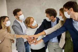 équipe masquée mettant les mains ensemble en se regardant photo