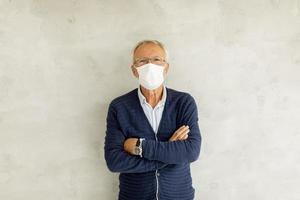 homme masqué mature avec les bras croisés photo
