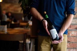 homme tenant une bouteille de vin photo